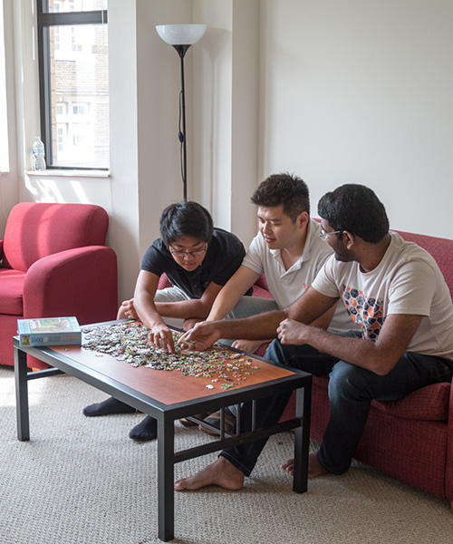 Residents working on a puzzle in their living room
